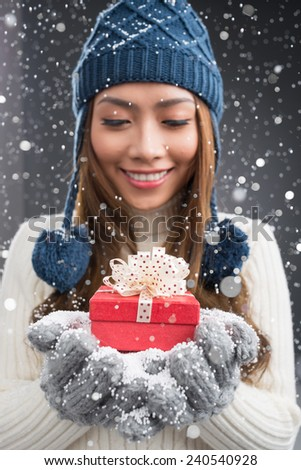 Cheerful young woman standing under the falling snow with a Christmas present - stock photo