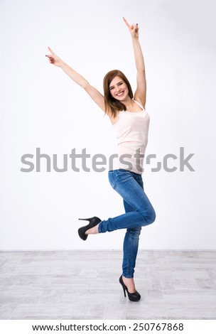 Cheerful young woman standing with raised hands up at the studio - stock photo