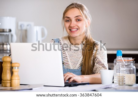 Cheerful young woman studing on laptop at domestic kitchen - stock photo