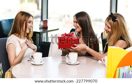 Cheerful young woman surprising friend with a gift in cafe