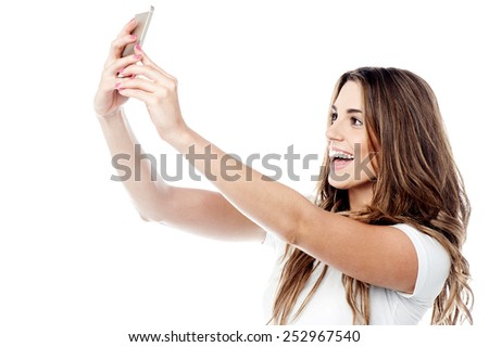 Cheerful young woman taking a picture of herself - stock photo