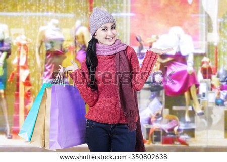 Cheerful young woman wearing sweater in the shopping center while holding shopping bags - stock photo
