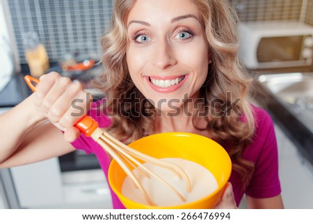 Cheerful Young woman whisking batter on a modern kitchen. Top view.  - stock photo