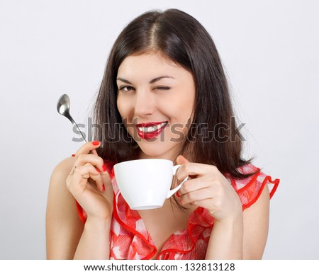 Cheerful young woman with a cup of coffee on a white background.