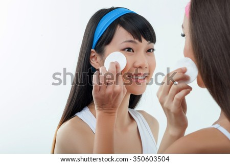 Cheerful young woman with asian and Caucasian appearance are smiling. They are standing and touching sponge to their faces. Isolated and copy space in left side - stock photo