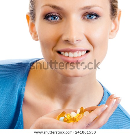Cheerful young woman with assorted pills and capsules, isolated over white background - stock photo