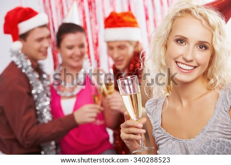 Cheerful young woman with flute of champagne looking at camera