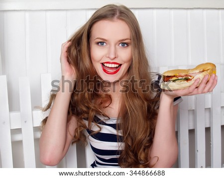 Cheerful young woman with long hair is eating the sandwich - stock photo