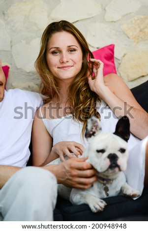 cheerful young woman with pet french bulldog in sofa outdoor - stock photo