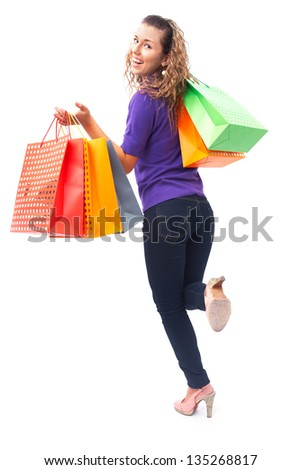 cheerful young woman with shopping bags hurries to the shopping