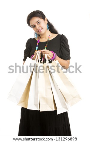 Cheerful Young woman with shopping bags over white background
