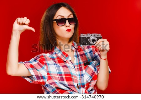 Cheerful young woman, with short dark hair, wearing in checkered shirt and black sunglasses, holding retro camera in her hand, on red background, in studio, waist up - stock photo
