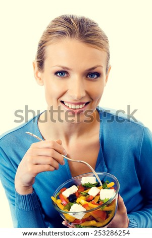 Cheerful young woman with vegeterian salad. Beauty and healthy eating concept.