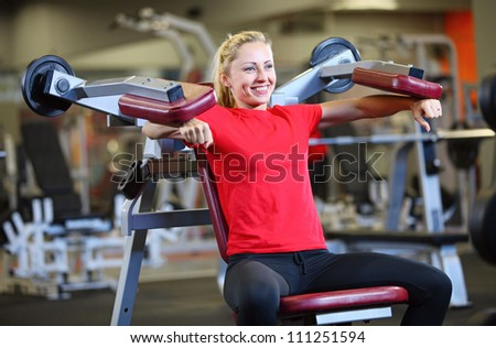 Cheerful young woman working out on exercise machine - stock photo