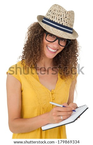 Cheerful young woman writing in notepad over white background - stock photo