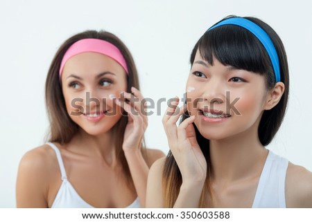 Cheerful young women are applying cream on their faces. They are standing and smiling. The ladies are looking forward happily. Isolated - stock photo