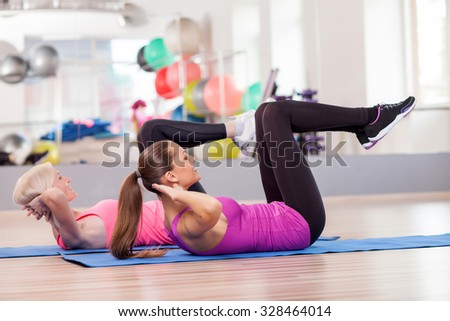 Cheerful young women are doing sit-ups in fitness center. They are lying and raising legs up. The girls are smiling - stock photo