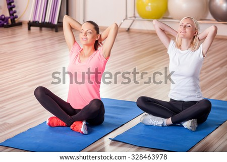 Cheerful young women are exercising at gym. They are sitting on carpets in lotus position and smiling. Their eyes are closed with relaxation