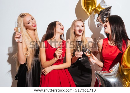 Cheerful young women drinking champagne, talking and laughing on the party over white background