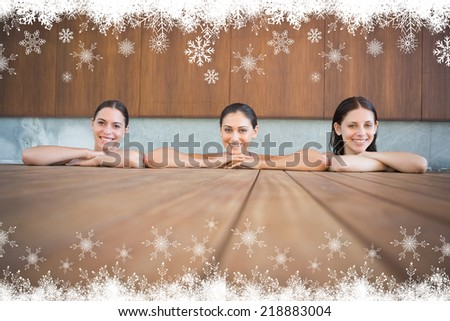 Cheerful young women in swimming pool against fir tree forest and snowflakes - stock photo