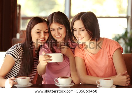 Cheerful young women taking selfie while drinking coffee in cafe
