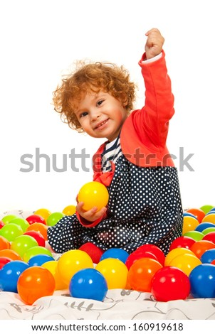 Cheerfullittle girl with balls sitting down against white background - stock photo