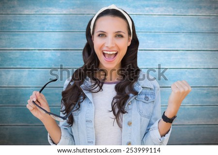 Cheering brunette against wooden planks - stock photo
