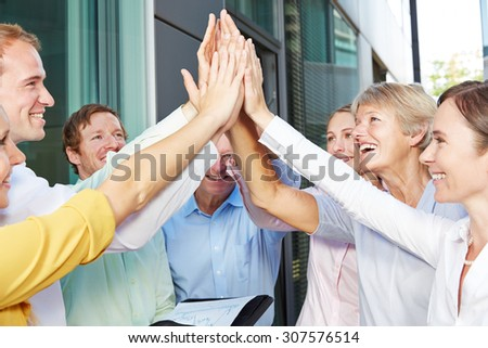 Cheering business people giving high five with their hands outside the office - stock photo