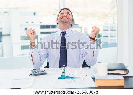 Cheering businessman at his desk in his office - stock photo