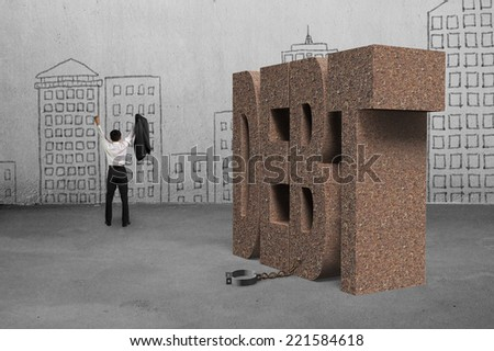 cheering businessman free from DEBT shackle with doodles wall - stock photo