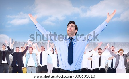 Cheering businessman with his arms raised up against cityscape on the horizon - stock photo