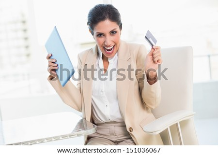 Cheering businesswoman shopping online with tablet pc in her office