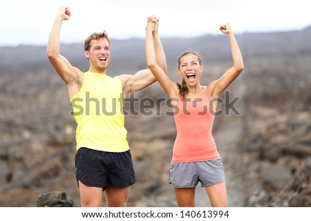 Cheering celebrating happy fitness runner couple with arms raised up in winning gesture expression outdoors on trail running path on Hawaii. Cheerful interracial couple, Asian woman, Caucasian man. - stock photo