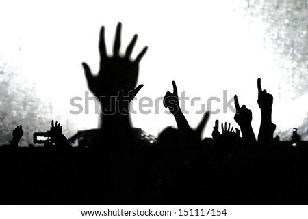 cheering crowd at a rock concert.silhouettes of hands up