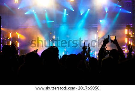 Cheering crowd in front of bright colorful stage lights - stock photo