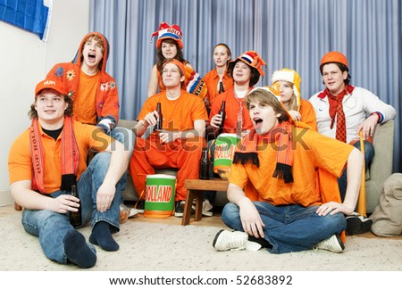 Cheering fans watching the game at home - stock photo