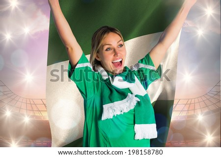 Cheering football fan in green jersey holding nigeria flag against large football stadium under bright blue sky - stock photo