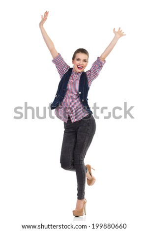 Cheering girl. Happy young woman is standing on one leg with arms raised. Full length studio shot isolated on white. - stock photo