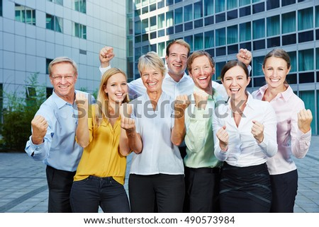 Cheering happy business people team clenching their fists next to the office