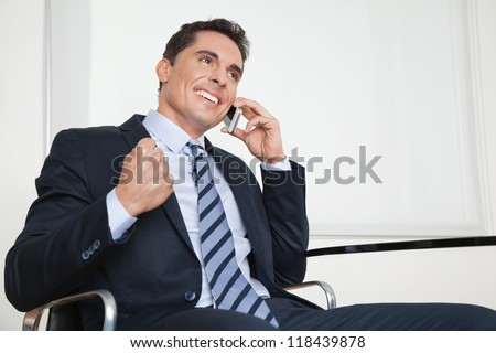 Cheering happy businessman with smartphone clenching his fist - stock photo