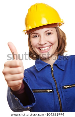 Cheering happy craftswoman in blue boiler suit holding thumbs up - stock photo