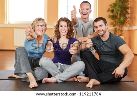 Cheering happy fitness group holding their thumbs up in a gym - stock photo