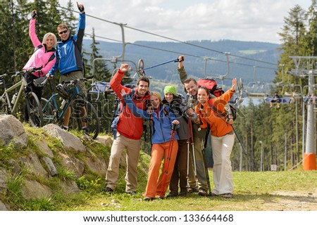 Cheering hikers with raised arms at peak of the mountain - stock photo