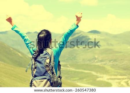 cheering hiking woman enjoy the beautiful view at mountain peak in tibet,china  - stock photo