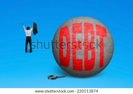 cheering man free from debt ball shackle isolated on blue - stock photo