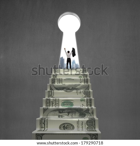 Cheering on top of money stairs with key hole city building outside - stock photo