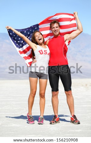 Cheering people athletes holding american USA flag celebrating happy with winning gesture after running. Young multicultural fitness runner couple in excited celebration outside in warm desert nature. - stock photo
