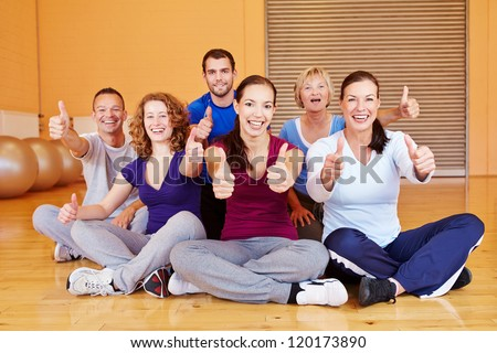 Cheering sports group holding thumbs up in a fitness center - stock photo