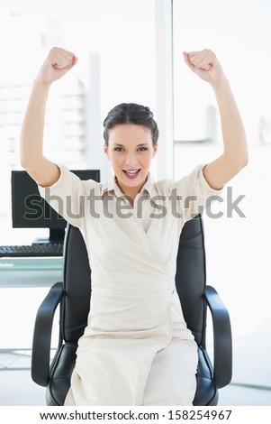 Cheering stylish brunette businesswoman raising her arms in bright office