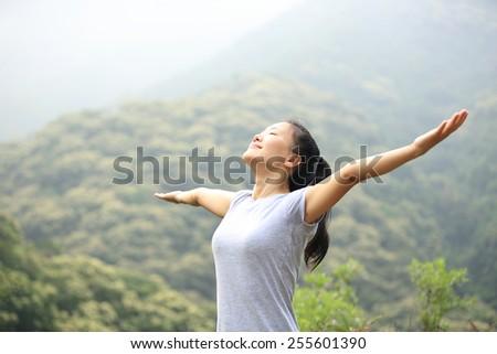 cheering woman enjoy the beautiful view at mountain peak  - stock photo